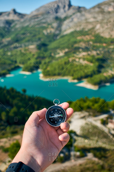 A man's hand holding a compass with a lake on background