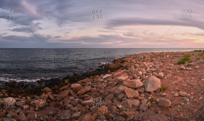 Panorama of a fantastic coast with a cloudscape at sunset