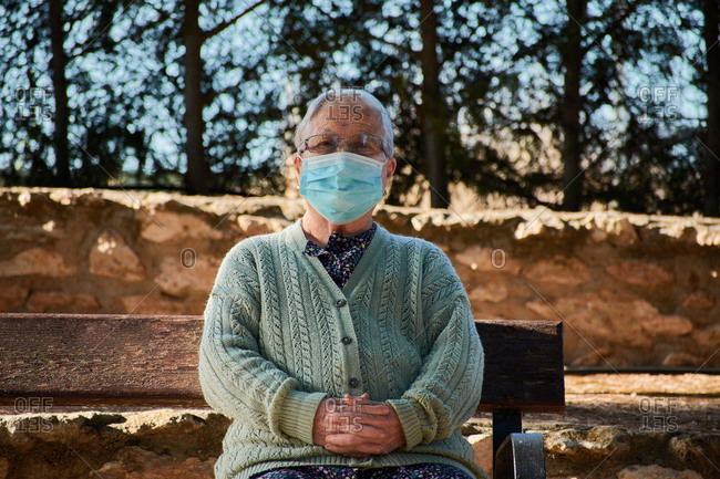 Older woman sitting on a park bench with her mask on looking at camera