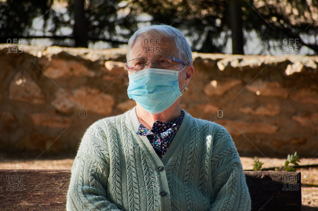 Older woman sitting on a park bench with her mask on