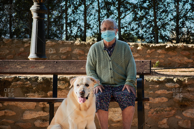 Grandmother with her pet is sitting on a bench with her mask on