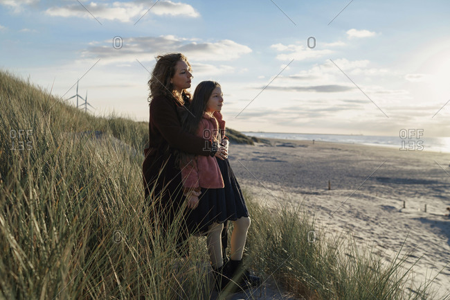 Mother and daughter standing on the beach against seascape view