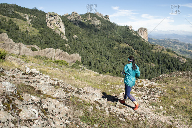 Mineral del Chico, Hgo., Mexico - September 30, 2018: One woman running on a rocky trail in Mineral del Chico