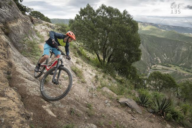 Mexico, Hidalgo, Huasca de Ocampo - September 29, 2018: One man riding down a mountain bike on a trail at a canyon