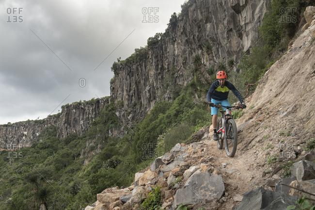 Mexico, Hidalgo, Huasca de Ocampo - September 29, 2018: A man riding down a mountain bike on a narrow rocky trail at a canyon