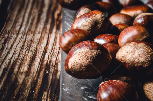 Close-up of several chestnuts in a glass dish, on a wooden table.