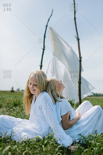 Two fair-haired girls in the summer sit on the grass and laugh