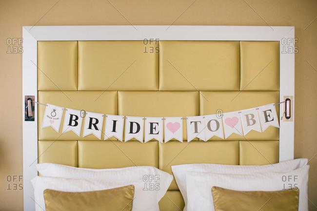 Marriage slogan written on cards. Bride to be written headboard.