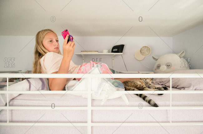 Tween Girl Lounging on Loft Bed Looking at Phone Cat in Foreground