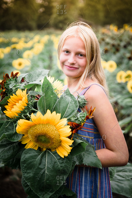 Young Girl Holding Red and Yellow Sunflowers in a Sunflower Field