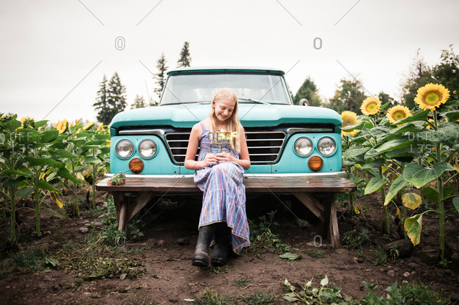 Young Girl Holding Sunflower by Vintage Truck in Sunflower Field