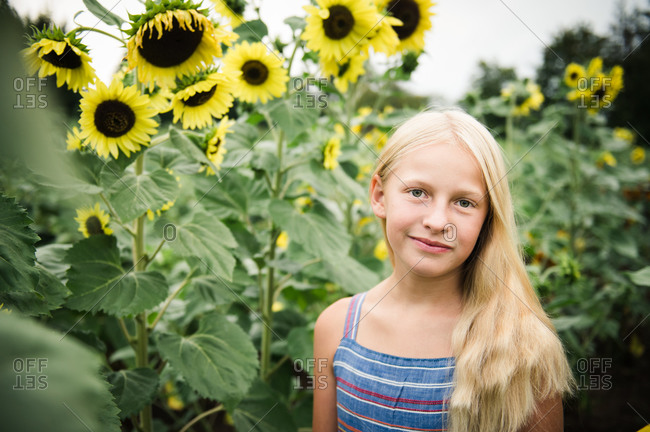 Young Girl Standing in Sunflower Field Next to Tall Yellow Sunflowers
