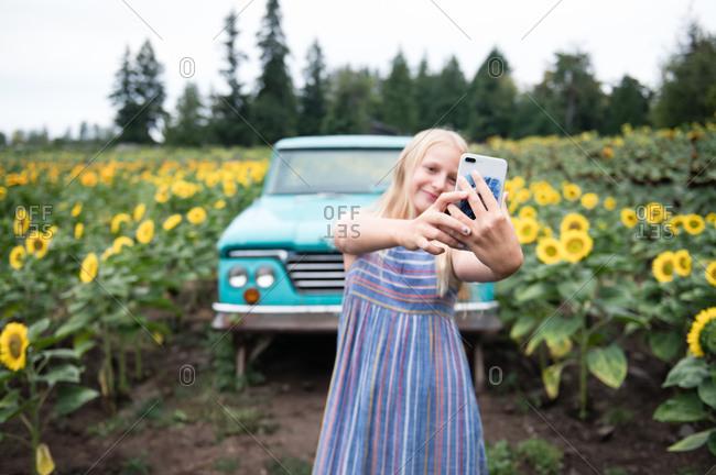 Tween Girl Holding Phone Taking Selfie in Sunflower Field with Truck
