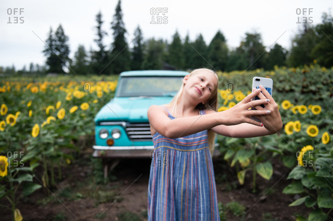 Young Girl Taking Selfie With Mobile Phone Standing on Sunflower Farm