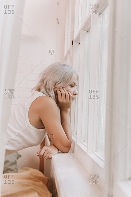 Beautiful woman opening curtains and looking through the window