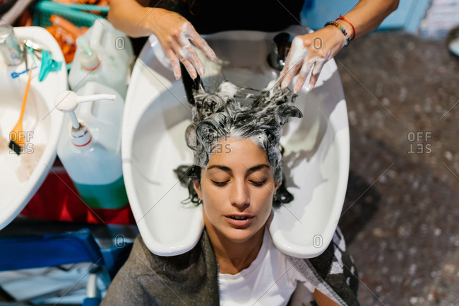 Woman in the hairdresser's shop shampooing her hair