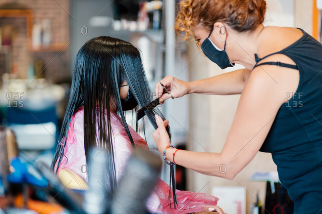 Woman in the hairdresser's with a mask, cutting her hair