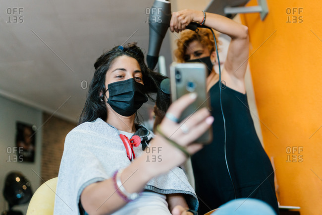 Woman in the hairdresser's with mask, cutting her hair, beauty salon