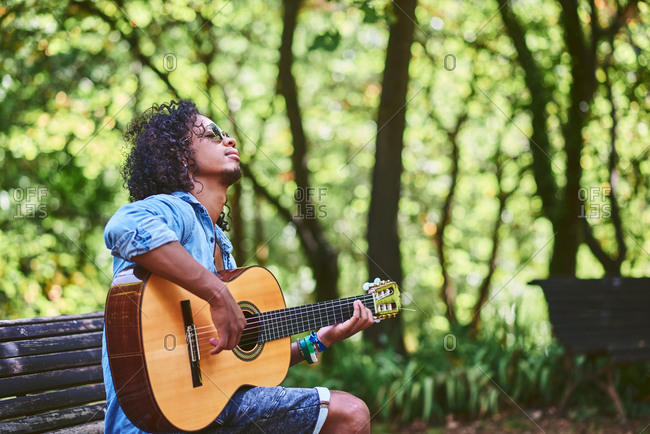 Musician playing guitar in a nice park. He is surrounded by vegetation.