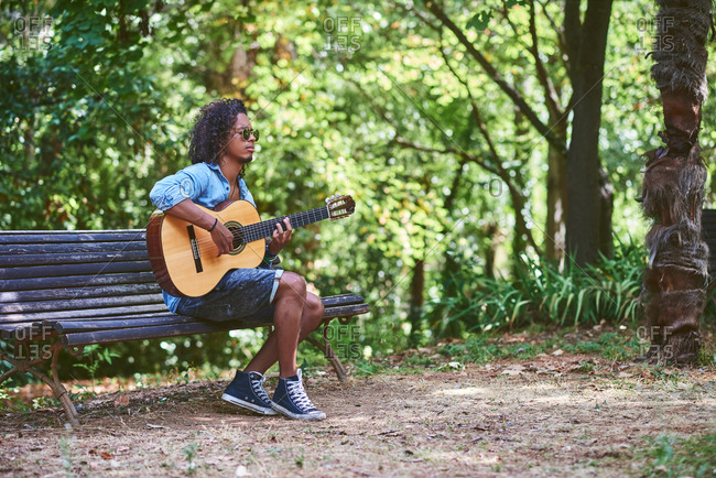 Musician playing guitar in a nice park.