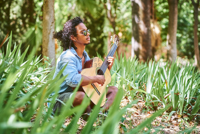 Musician practicing with the guitar in the field.
