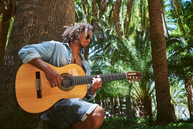 Young musician with classical guitar playing under the shade of some trees in a park.