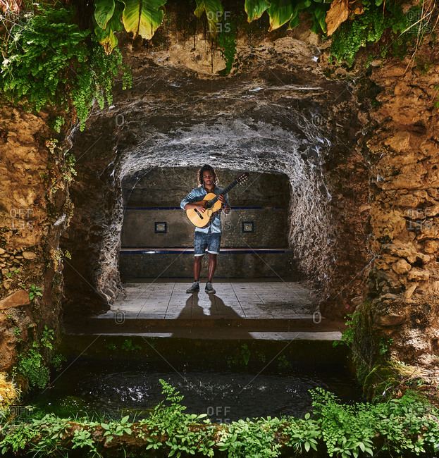 Musician with classical guitar playing in a cave.