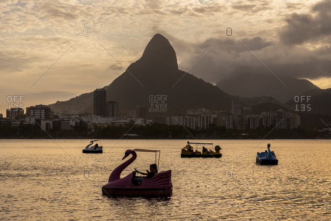 Rio de Janeiro, RJ, Brazil - October 18, 2020: Beautiful view to pedal boats on city lagoon with mountains on sunset