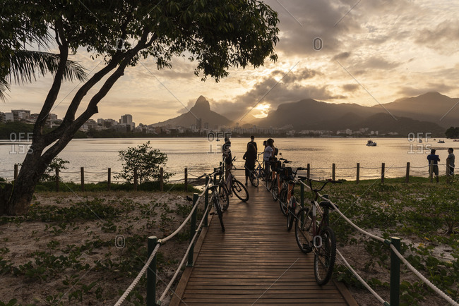 Rio de Janeiro, RJ, Brazil - October 18, 2020: Beautiful view to group of friends by city lagoon on sunset time