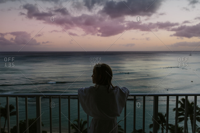 Young girl in bathrobe watches ocean at sunset from balcony in Hawaii