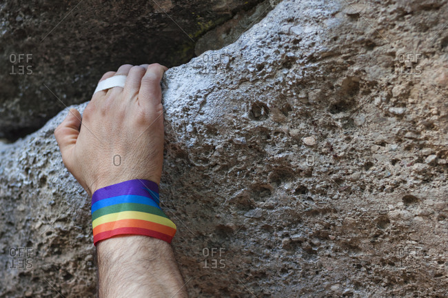 Climbing hand with gay pride bracelet