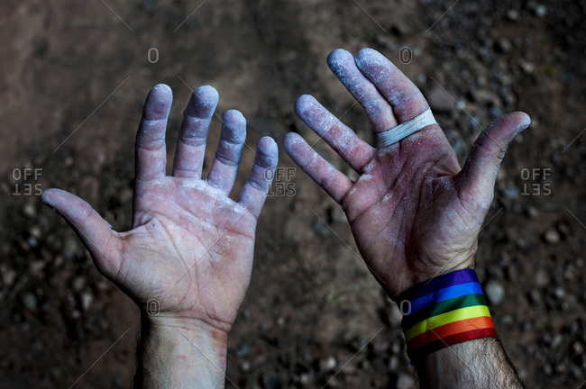 Look at the hands and fingers of a climber with the gay pride bracelet, after finishing the climb.