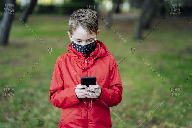 Boy in red jacket playing with his smartphone