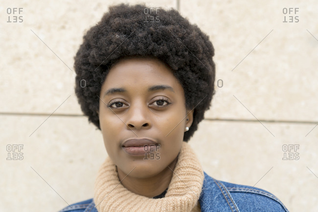 Photography of elegant African woman with afro hair and blue windbreaker