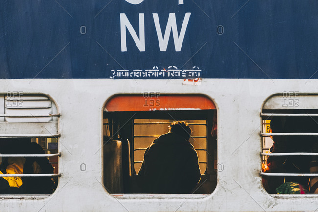 New Delhi, DL, India - January 20, 2018: Young man looking through train window, sleeper class category from New Delhi to Agra,