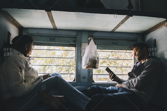 Agra, UP, India - January 21, 2018: Indian couple sitting on a berth on a commute train from New Delhi to Agra.