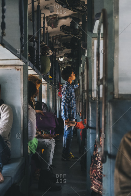 Agra, UP, India - January 21, 2018: Young boy talking with his mum sitting on a berth on top while traveling from New Delhi to Agra, Sleeper Class Train.