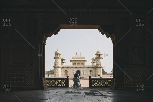 Young woman sitting at the entrance gate of the Tomb of Itmad-ud-Daula with the mausoleum in the background.