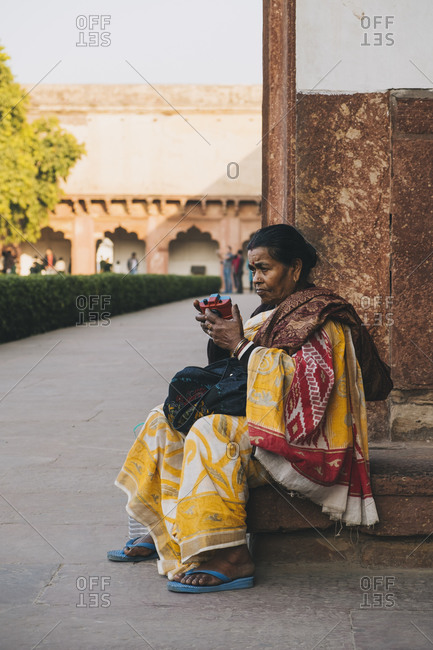 Agra, UP, India - January 22, 2018: Indian woman playing with toy camera dressed in yellow sari at the Agra Fort Entrance.