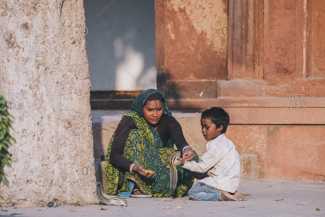 Agra, UP, India - January 22, 2018: Indian woman and her son feeding a couple squirrel by the Agra fort.