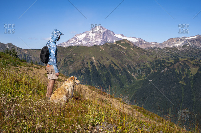 Male hiker and dog with glacier peak in the distance