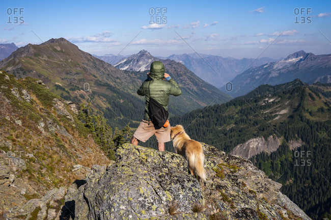 Male hiker and dog taking in the view from the summit