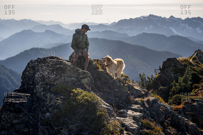 Male hiker and dog in the cascades with smokey views