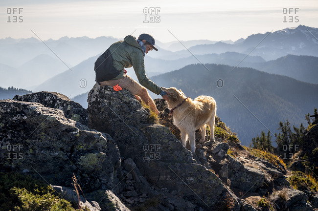 Male hiker and dog on summit of mountain in the cascades