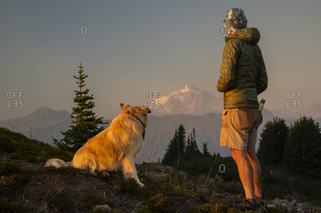 Dog and Male Hiker watching the light fade on glacier peak