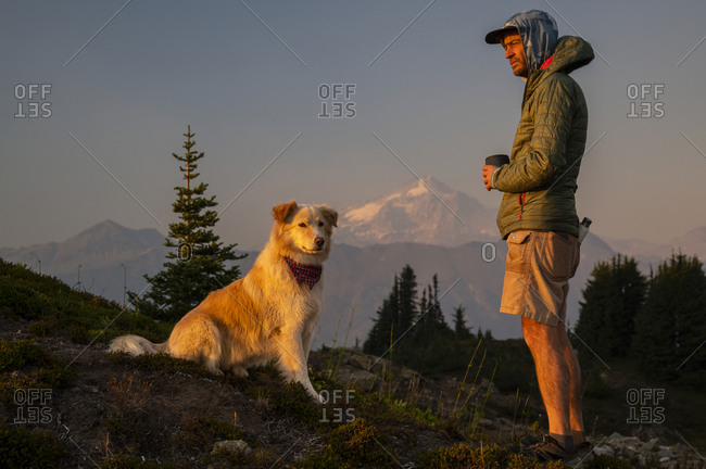 Dog and hiker at sunset with volcano in the distance