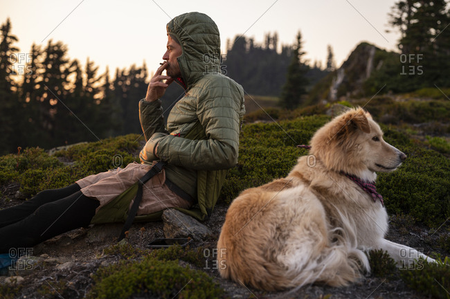Male smoking cigarette with cute dog in the cascade mountain alpine
