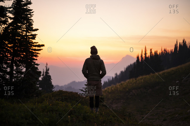Silhouette of male watching colorful sunset in the cascade mountains