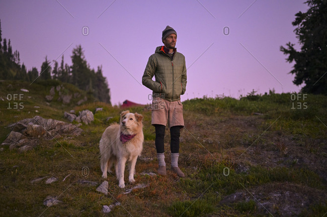Dog and male in puffy coat watching the sunset with purple sky