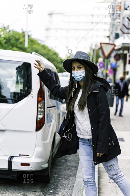 Young woman in the city wearing face mask and hailing a taxi cab